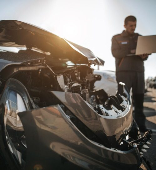 mechanic-working-on-laptop-in-front-of-damaged-car-on-parking-lot-picture-id1182002245.1